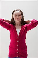 preteen girls stretching - Girl in red with hands behind head, studio shot Stock Photo - Premium Royalty-Freenull, Code: 614-06002449