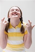 Girl with fingers crossed, studio shot Stock Photo - Premium Royalty-Freenull, Code: 614-06002461