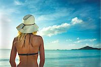 Rear view of woman in sunhat looking out to sea Stock Photo - Premium Royalty-Freenull, Code: 614-06002605