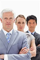 Close-up of a business man with subordinates behind him against white background Stock Photo - Premium Royalty-Freenull, Code: 6109-06002723