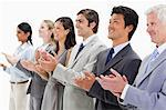Smiling multicultural business people applauding against white background Stock Photo - Premium Royalty-Free, Artist: I Dream Stock, Code: 6109-06002763