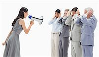 Woman yelling in a megaphone at business people against white background Stock Photo - Premium Royalty-Freenull, Code: 6109-06002789