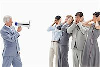 Man yelling in a megaphone at business people with their hands over their ears against white background Stock Photo - Premium Royalty-Freenull, Code: 6109-06002793