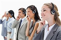 Smiling professionals with headsets against white background Stock Photo - Premium Royalty-Freenull, Code: 6109-06002809