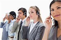 Professionals listening carefully with headsets against white background Stock Photo - Premium Royalty-Freenull, Code: 6109-06002815