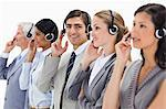 Close-up of professionals in suits listening with headsets against white background Stock Photo - Premium Royalty-Freenull, Code: 6109-06002819
