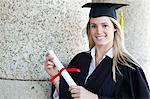 Happy graduating student wearing a gown while proudly holding her diploma Stock Photo - Premium Royalty-Freenull, Code: 6109-06003569