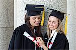 Young happy graduating girls looking at a digital camera while holding their diplomas Stock Photo - Premium Royalty-Free, Artist: Blend Images, Code: 6109-06003579