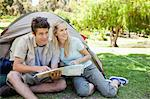 A smiling camping couple look at something over in the distance as they hold a map Stock Photo - Premium Royalty-Free, Artist: Blend Images, Code: 6109-06003875