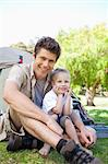 A smiling dad and son sit together just outside of the tent Stock Photo - Premium Royalty-Free, Artist: R. Ian Lloyd, Code: 6109-06003917