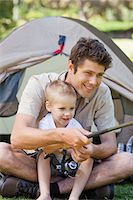 fishing - A close up shot of a dad and his boy fishing by the tent Stock Photo - Premium Royalty-Freenull, Code: 6109-06003923