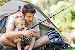 A father and son near the tent try to catch fish together Stock Photo - Premium Royalty-Free, Artist: Blend Images, Code: 6109-06003927