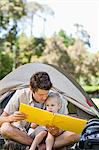 A dan and hid boy read a large book together by the tent Stock Photo - Premium Royalty-Free, Artist: R. Ian Lloyd, Code: 6109-06003929