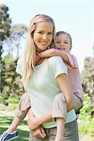 A portrait shot of a mother carrying her daughter on her back in the park Stock Photo - Premium Royalty-Freenull, Code: 6109-06003994