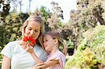 A mother looking at the pretty flower her daughter is holding Stock Photo - Premium Royalty-Free, Artist: Beanstock Images, Code: 6109-06004001