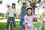 A smiling family on their bikes wearing helmets in the park Stock Photo - Premium Royalty-Free, Artist: GreatStock, Code: 6109-06004032