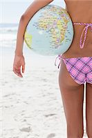 Rear view of a young woman holding a globe beach ball while standing on the beach Stock Photo - Premium Royalty-Freenull, Code: 6109-06004139