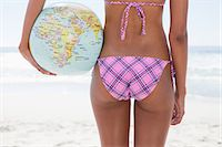 Young woman holding a globe beach ball while standing in front of the ocean Stock Photo - Premium Royalty-Freenull, Code: 6109-06004140