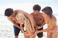 Woman in a bikini smiling as she tussles with her friends for a white football on the beach Stock Photo - Premium Royalty-Freenull, Code: 6109-06004246