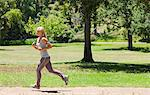 Side view of a jogging young woman Stock Photo - Premium Royalty-Free, Artist: CulturaRM, Code: 6109-06004310