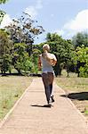 Rear view of a jogging young woman Stock Photo - Premium Royalty-Free, Artist: Blend Images, Code: 6109-06004317