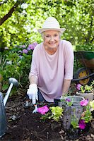Woman smiling happily while planting pink flowers in her garden Stock Photo - Premium Royalty-Freenull, Code: 6109-06004610