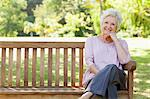 Woman smiling joyfully as she leans on the arm of a bench while sitting on a bench Stock Photo - Premium Royalty-Free, Artist: AWL Images, Code: 6109-06004661