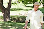 Man wearing a hat and smiling with a cane in his hand in a park Stock Photo - Premium Royalty-Free, Artist: Zoran Milich, Code: 6109-06004703