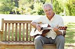 Man looking ahead of him as he plays a song on a guitar as he sits on a bench in the park Stock Photo - Premium Royalty-Free, Artist: Blend Images, Code: 6109-06004751