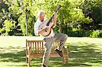 Man plays a guitar while standing with a leg raised in front of a bench in a park Stock Photo - Premium Royalty-Free, Artist: Blend Images, Code: 6109-06004769