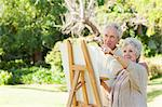 Man and a woman smiling while painting on a canvas in a park Stock Photo - Premium Royalty-Free, Artist: CulturaRM, Code: 6109-06004815