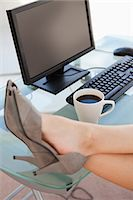 Close-up on the businesswoman's feet on a glass desk next to a coffee Stock Photo - Premium Royalty-Freenull, Code: 6109-06005473