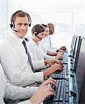 Young call center employee sitting among his colleagues Stock Photo - Premium Royalty-Free, Artist: Blend Images, Code: 6109-06005817