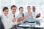 Side view of applauding young salesteam sitting at a table Stock Photo - Premium Royalty-Freenull, Code: 6109-06005843