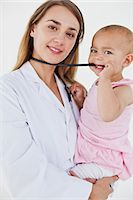 Lovely baby chewing the stethoscope of the nurse who is holding her Stock Photo - Premium Royalty-Freenull, Code: 6109-06007094