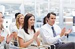 Colleagues looking ahead and applaud as they sit next to each other Stock Photo - Premium Royalty-Free, Artist: Ikonica, Code: 6109-06007211