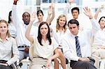 Serious colleagues sit together as they raise their arms above their head Stock Photo - Premium Royalty-Freenull, Code: 6109-06007215