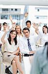 A group of co-workers raising their hands as they watch as speaker Stock Photo - Premium Royalty-Free, Artist: Blend Images, Code: 6109-06007229