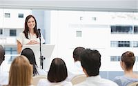 Brunette businesswoman giving a speech while she is being watched by her colleagues Stock Photo - Premium Royalty-Freenull, Code: 6109-06007329