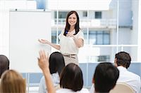 Woman smiling as she gestures to a member of the audience that has her hand raised Stock Photo - Premium Royalty-Freenull, Code: 6109-06007335