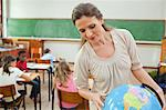 Elementary teacher looking at globe in classroom Stock Photo - Premium Royalty-Free, Artist: CulturaRM, Code: 6109-06007575