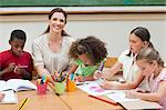 Smiling elementary teacher paining together her students Stock Photo - Premium Royalty-Freenull, Code: 6109-06007583