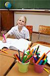 Smiling little girl sitting at desk next to pen holders Stock Photo - Premium Royalty-Freenull, Code: 6109-06007604