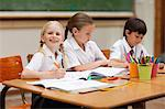 Smiling little girl sitting next to schoolfellows Stock Photo - Premium Royalty-Freenull, Code: 6109-06007610