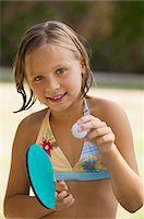 Girl (7-9) wearing bikini holding table tennis paddle and ball, portrait. Stock Photo - Premium Royalty-Freenull, Code: 693-06013550