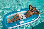 Boy (13-15) Relaxing on Inflatable Raft in swimming pool, elevated view. Stock Photo - Premium Royalty-Free, Artist: AlaskaStock, Code: 693-06013568