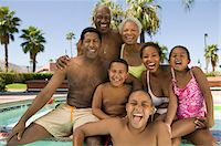 Girl (5-6), boy (7-9), boy (10-12), with parents and grandparents at swimming pool, front view portrait. Stock Photo - Premium Royalty-Freenull, Code: 693-06013570
