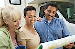 Friends studying road map beside motor home Stock Photo - Premium Royalty-Free, Artist: Cultura RM, Code: 693-06013701