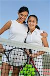 Mother and daughter standing at net on tennis court, portrait, low angle view Stock Photo - Premium Royalty-Free, Artist: Bettina Salomon, Code: 693-06013823