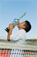 preteen kissing - Young tennis player by net on court kissing trophy, side view Stock Photo - Premium Royalty-Freenull, Code: 693-06013828